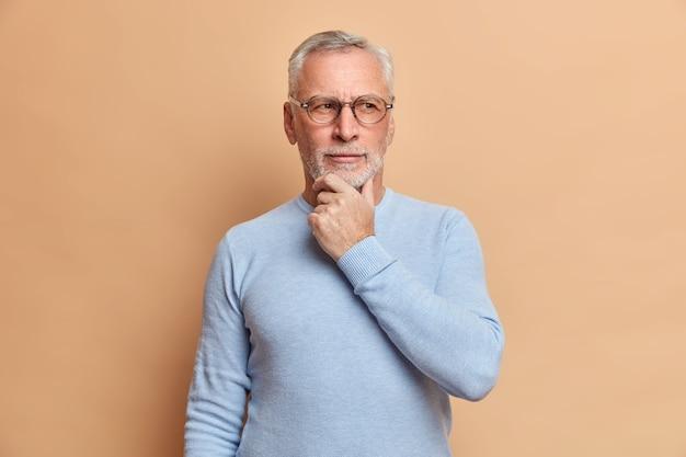 Студийный снимок вдумчивого пожилого мужчины, держащего подбородок и размышляющего о чем-то небрежно одетом, пытается что-то вспомнить и собраться с мыслями, позирует на коричневой стене