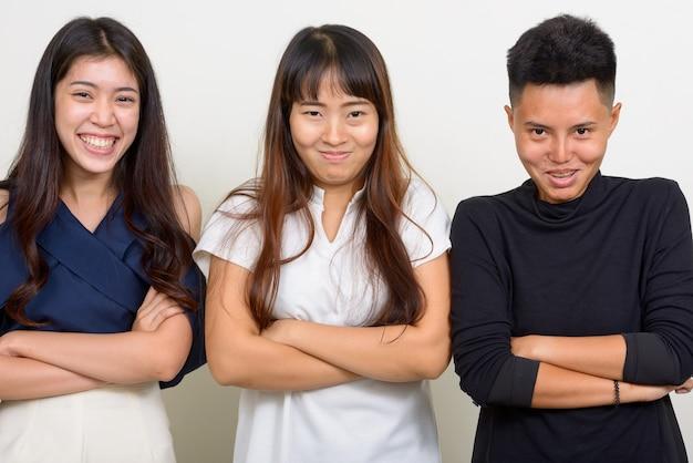 Студия выстрел из трех молодых красивых азиатских женщин как друзей вместе на белом фоне