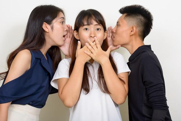 白い背景に対して一緒に友達として3人の若い美しいアジアの女性のスタジオショット