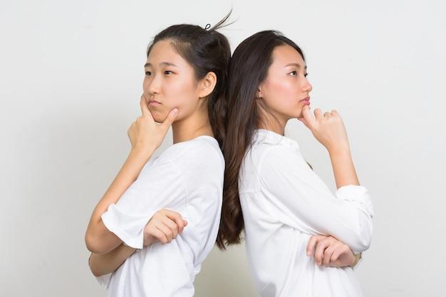 Студийный снимок двух молодых красивых корейских женщин как друзей вместе на белом фоне