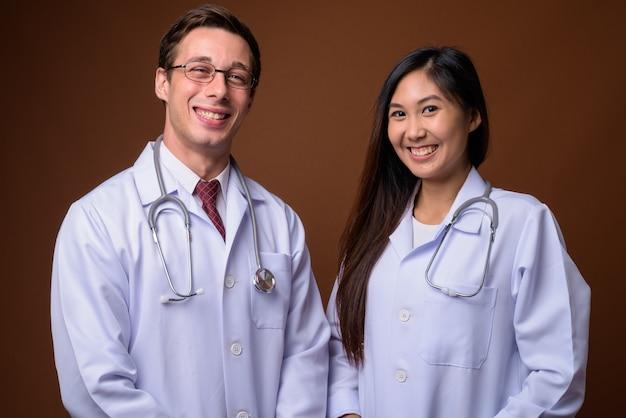 Студийный снимок двух молодых врачей вместе на коричневом му