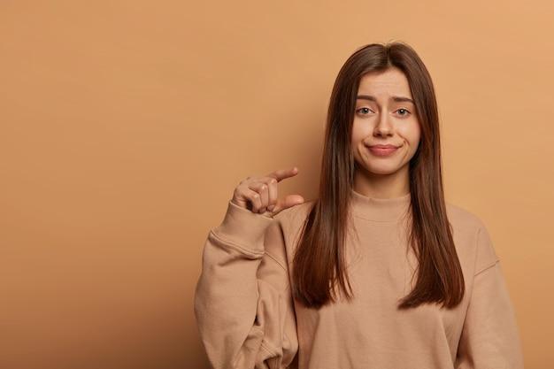 Студийный снимок не впечатленной красивой женщины, которая жестикулирует, демонстрирует крошечный предмет, носит свободную толстовку