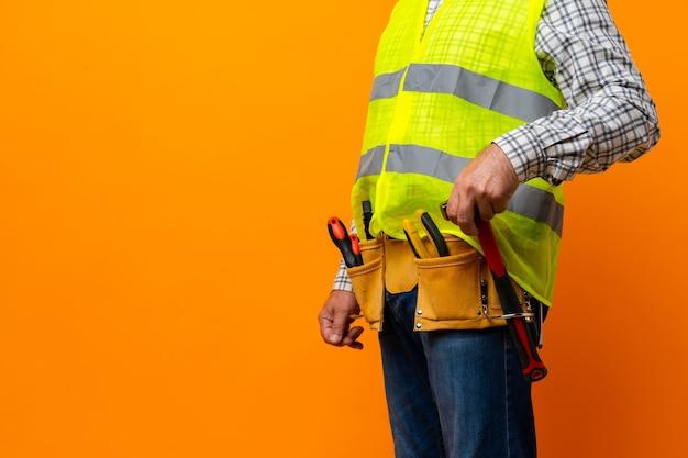 Студийный снимок неизвестного разнорабочего с руками на талии и поясом для инструментов со строительными инструментами