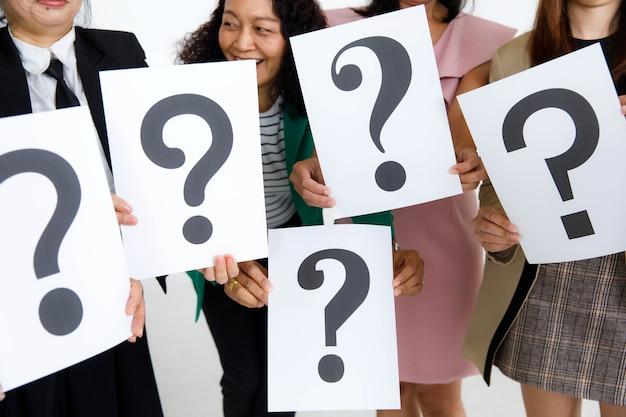비즈니스 정장을 입은 정체불명의 얼굴 없는 여성 직원의 스튜디오 샷은 흰색 배경에 대한 답이 의심스러운 손에 물음표 종이 사인의 다양한 글꼴을 들고 있습니다.