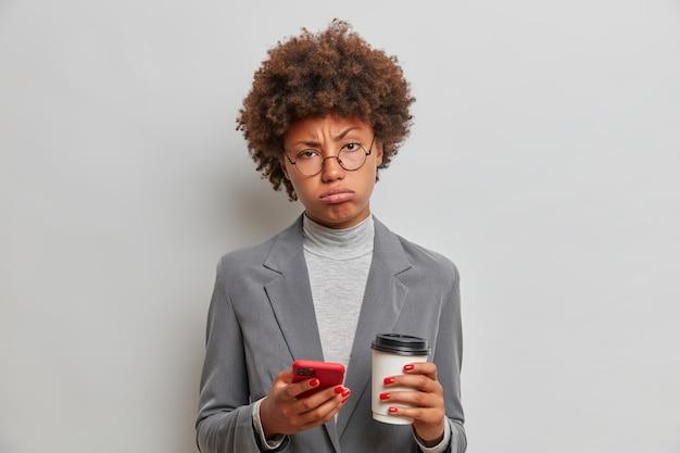 화가 피로 젊은 여성의 스튜디오 샷은 전면에 피곤한 표정으로 보이는 공식적인 회색 의상을 입은 상쾌한 커피는 온라인 뉴스를 확인하기 위해 현대 셀룰러를 사용합니다.