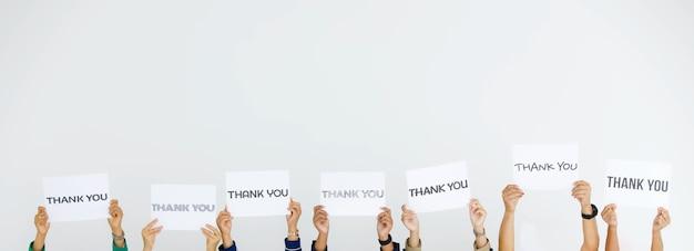 다양한 글꼴의 스튜디오 샷은 흰색 배경에서 고객에게 감사를 표하는 식별할 수 없는 얼굴 없는 직원 그룹이 머리 위에 들고 있는 편지 종이 사인에 감사합니다.