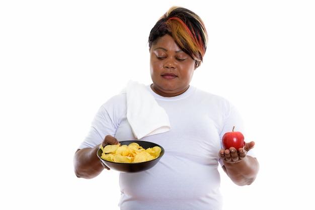 Студийный снимок женщины, смотрящей на миску картофеля