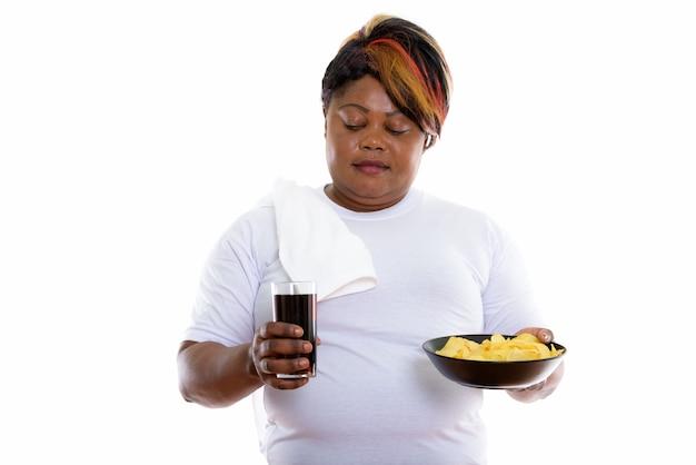 Студийный снимок женщины, смотрящей на стакан газировки