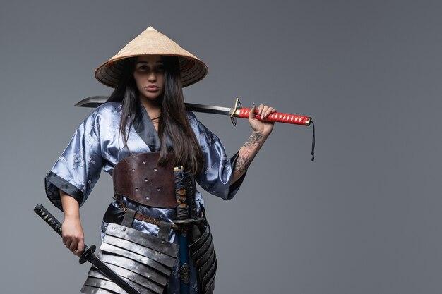 刀を肩に抱えた東からの女戦士のスタジオショット。