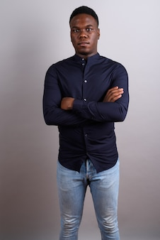 白い背景に青いシャツを着ている若いアフリカのビジネスマンのスタジオショット