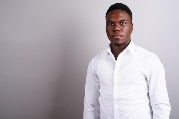 白い背景に白いシャツを着ている若いアフリカのビジネスマンのスタジオショット