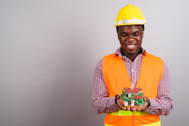白い背景の若いアフリカ人建設労働者のスタジオショット