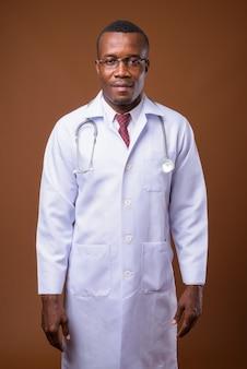 茶色の背景に対して若いアフリカ人医師のスタジオショット
