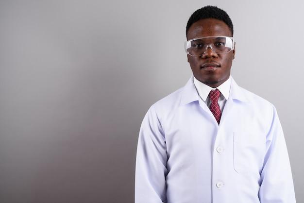 흰색 배경에 대해 보호 안경을 착용하는 젊은 아프리카 남자 의사의 스튜디오 샷