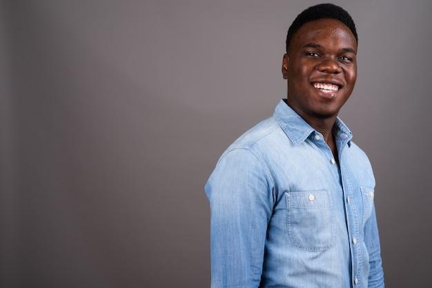 灰色の背景にデニムシャツを着ている若いアフリカ人のスタジオショット