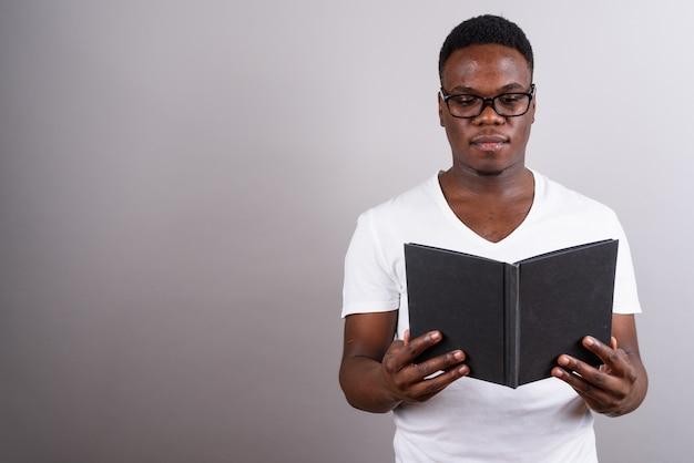 白い背景の本を読んでいる間眼鏡をかけている若いアフリカ人のスタジオショット