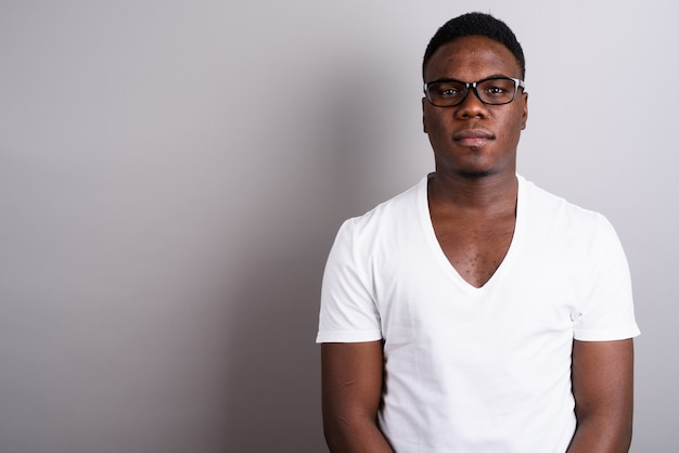 白い背景に白いシャツと眼鏡を身に着けている若いアフリカ人のスタジオショット
