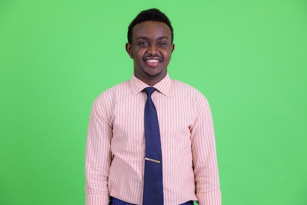緑の背景にアフロの髪を持つ若いアフリカ人のスタジオショット