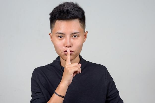 白い背景の短い髪の若いアジアのレズビアンの女性のスタジオショット