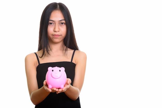 Студийный снимок молодой азиатской девочки-подростка, держащей копилку