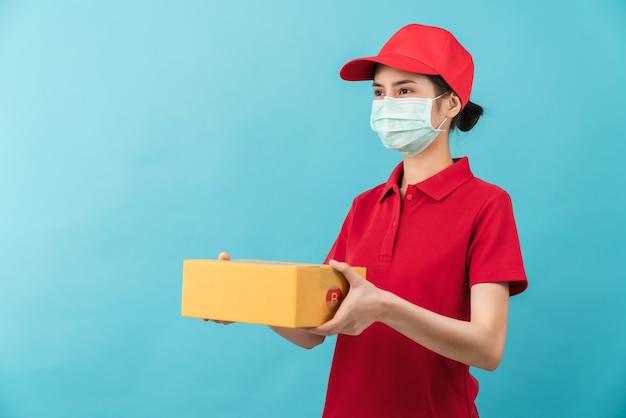 水色の背景にフェイスマスクと手持ちの段ボール箱を身に着けている赤いキャップシャツの制服を着た若いアジア人女性のスタジオショット、サービス検疫パンデミックウイルスの配達従業員。