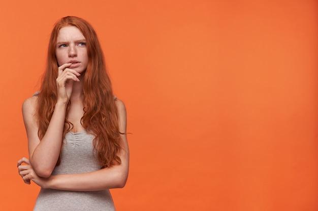 오렌지 배경 위에 서있는 캐주얼 옷을 입은 젊은 매력적인 빨간 머리 여성의 스튜디오 샷, 손으로 턱을 잡고 옆으로 생각을 모 으려고 노력하고 있습니다.
