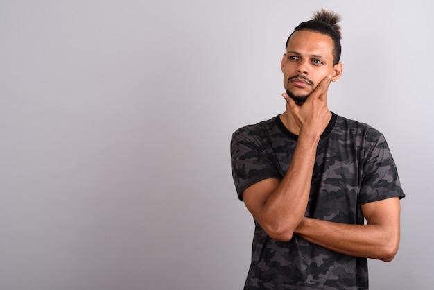灰色の背景に結ばれた髪のカモフラージュプリントシャツを着ている若いひげを生やしたハンサムなアフリカ人のスタジオショット