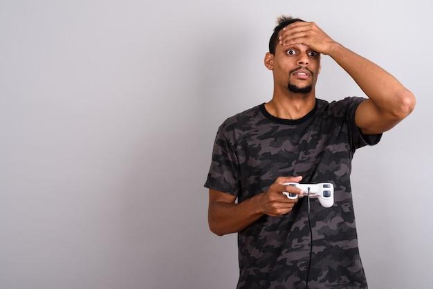 회색 배경에 묶여 머리와 위장 인쇄 셔츠를 입고 젊은 수염 잘 생긴 아프리카 남자의 스튜디오 샷