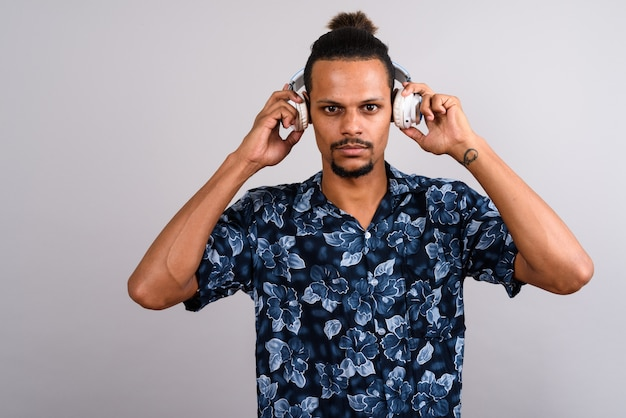 灰色の背景に音楽を聴きながらアロハシャツを着ている若いひげを生やしたハンサムなアフリカ人のスタジオショット