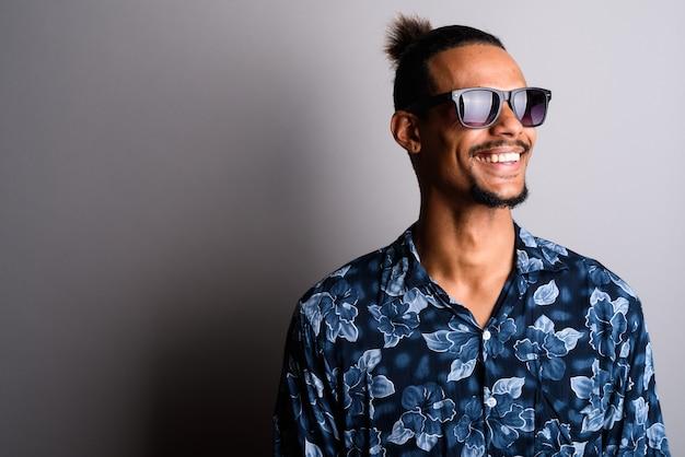 灰色の背景にサングラスをかけて若いひげを生やしたハンサムなアフリカ人のスタジオショット