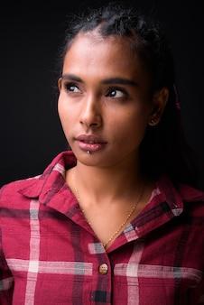 黒の背景に編みこみの髪を持つ若い美しいアジアの流行に敏感な女性のスタジオショット