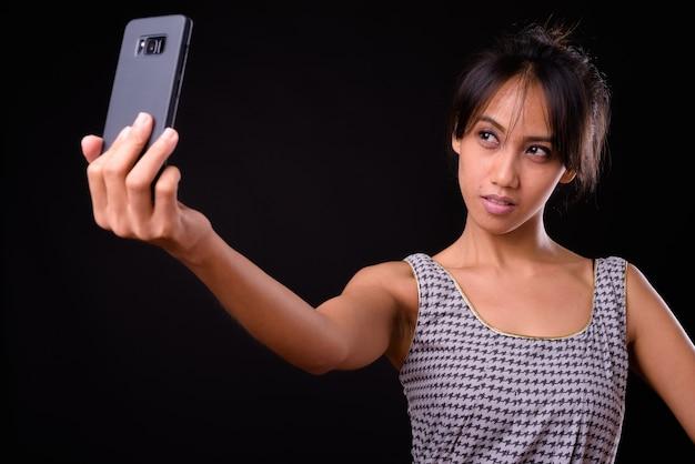 Студия выстрел молодой красивой филиппинской женщины на черном фоне