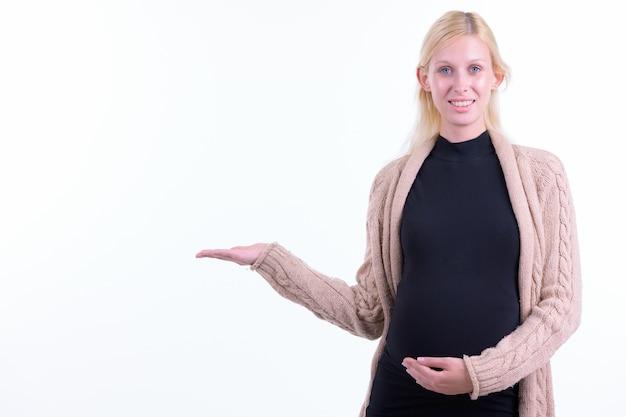 白い背景に対して隔離のブロンドの髪を持つ若い美しい妊婦のスタジオショット