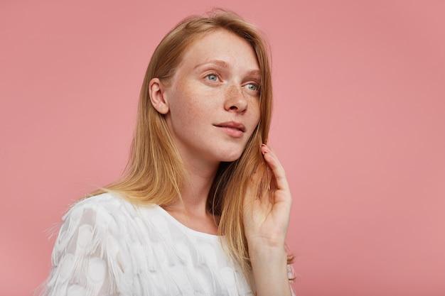 분홍색 배경 위에 포즈를 취하는 동안 흰색 티셔츠를 입고 꿈꾸게 옆으로 보면서 그녀의 얼굴에 손을 올리는 녹색 회색 눈을 가진 젊은 아름다운 빨간 머리 아가씨의 스튜디오 샷
