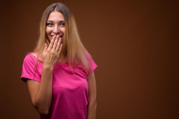 Студийный снимок молодой красивой женщины, смеющейся и закрывающей рот