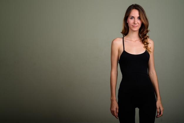 色付きの背景に対してノースリーブトップを着ている若い美しい女性のスタジオ撮影