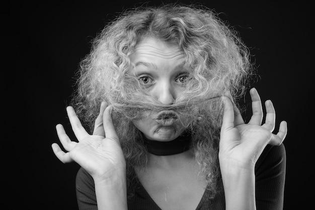 灰色の壁に金髪の巻き毛を持つ若い美しい女性のスタジオショット