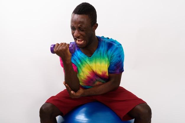 Студия выстрел молодого черного африканского фитнеса человека, сидящего на упражнениях