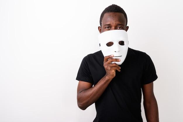 Студийный снимок молодого темнокожего африканца, держащего маску перед