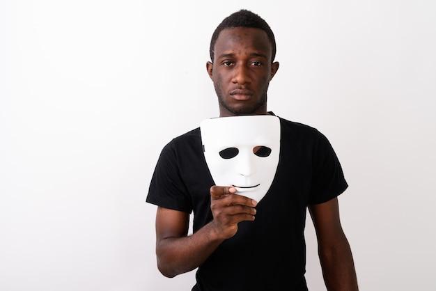 Студийный снимок молодого темнокожего африканца, держащего маску