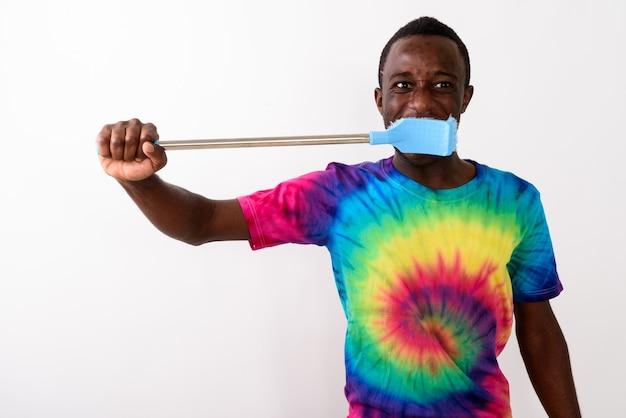 大きなクリーニングブラシを使用して若い黒人アフリカ人のスタジオショット