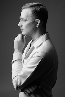 흑인과 백인 회색 벽에 보호 안경 젊은 금발 잘 생긴 남자 의사의 스튜디오 샷