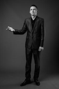 灰色の壁にスーツを着ている青年実業家のスタジオショット