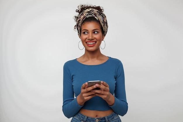 白い背景の上にポーズをとっている間、携帯電話を上げた手に保ちながら、脇を見ながら広く笑っている若い嬉しいかなり巻き毛のブルネットの女性のスタジオショット