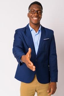 白い背景にアフロの髪を持つ若いハンサムなアフリカのビジネスマンのスタジオショット