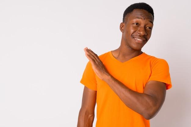 白い背景の上のアフロの髪を持つ若いハンサムなアフリカ人のスタジオショット