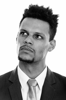 黒と白の白い背景に対して分離されたスーツの若いハンサムなひげを生やしたアフリカのビジネスマンのスタジオショット