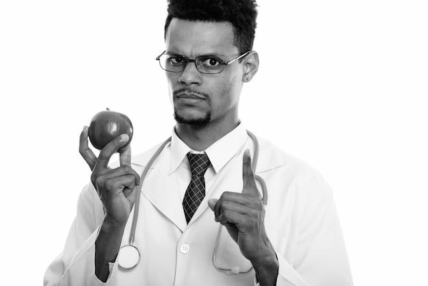 Студийный снимок молодого красивого бородатого африканца-доктора, изолированного на белом фоне в черно-белом