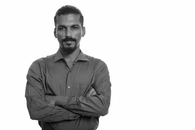 Студийный снимок молодого красивого бородатого индийского бизнесмена против белого в черно-белом