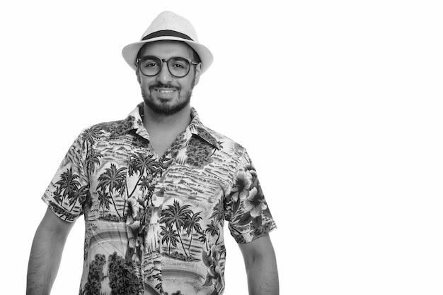 白と黒の休暇の準備ができているアロハシャツを着た若いハンサムなひげを生やしたインド人観光客のスタジオ ショット